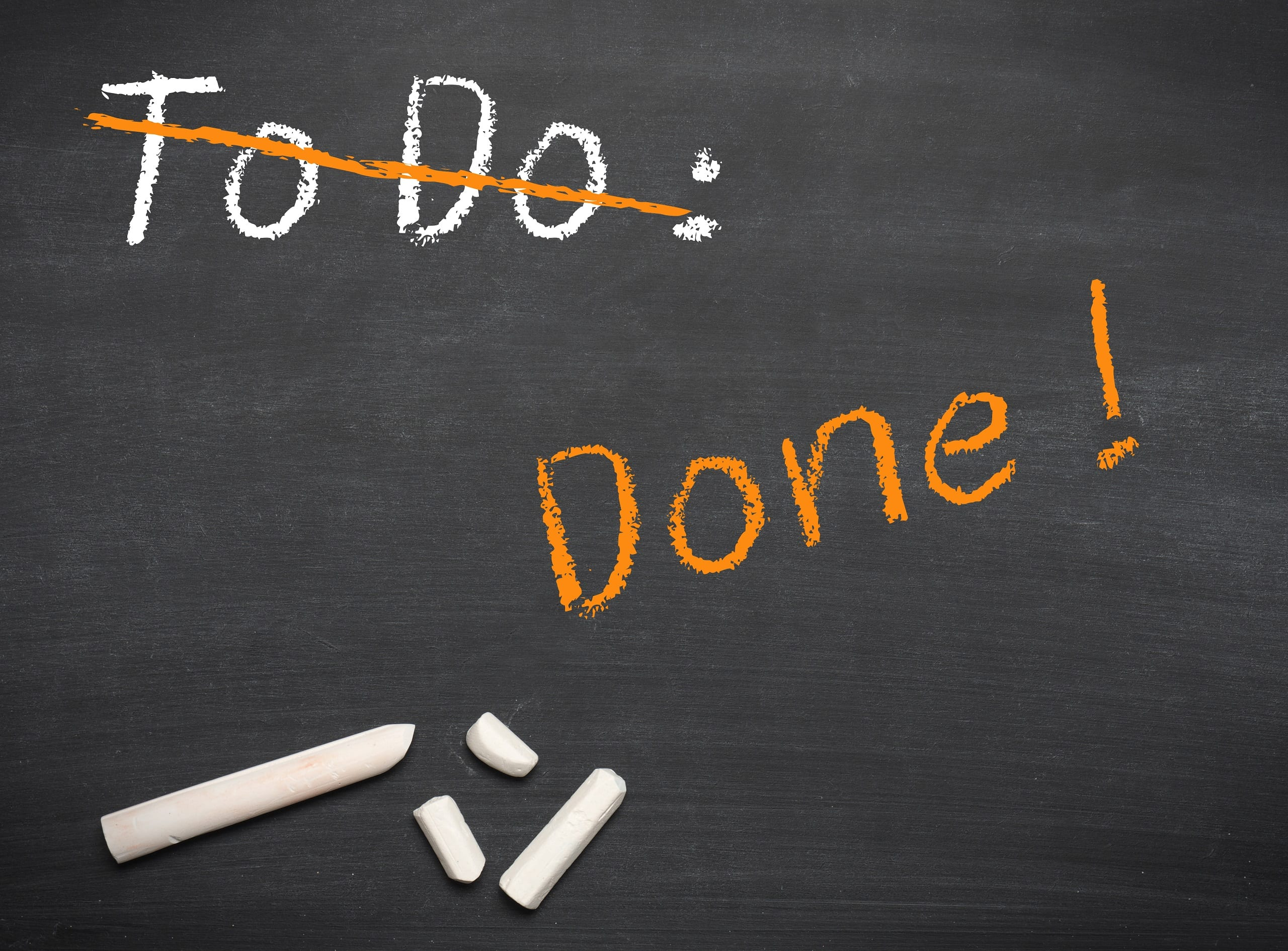 """A graphic of the words """"To Do"""" crossed out, with """"Done!"""" written and not crossed out in chalk. Symbolizes task completion."""