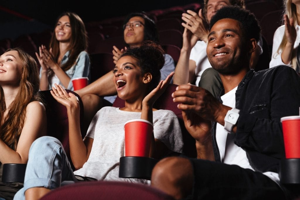 Multiethnic happy audience clapping hands while sitting at the cinema and watching movie.