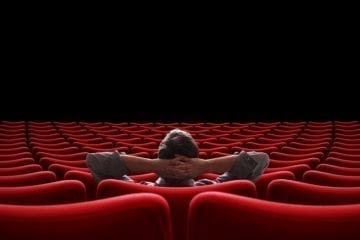 Empty movie theater with one man sitting comfortably inside staring at a dark empty screen.