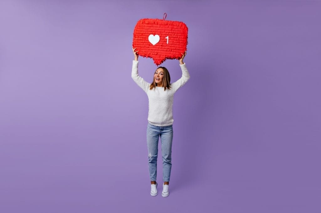 A woman standing in front of a purple background smiling while wearing casual clothes. Meant to represent Instagram Followers.
