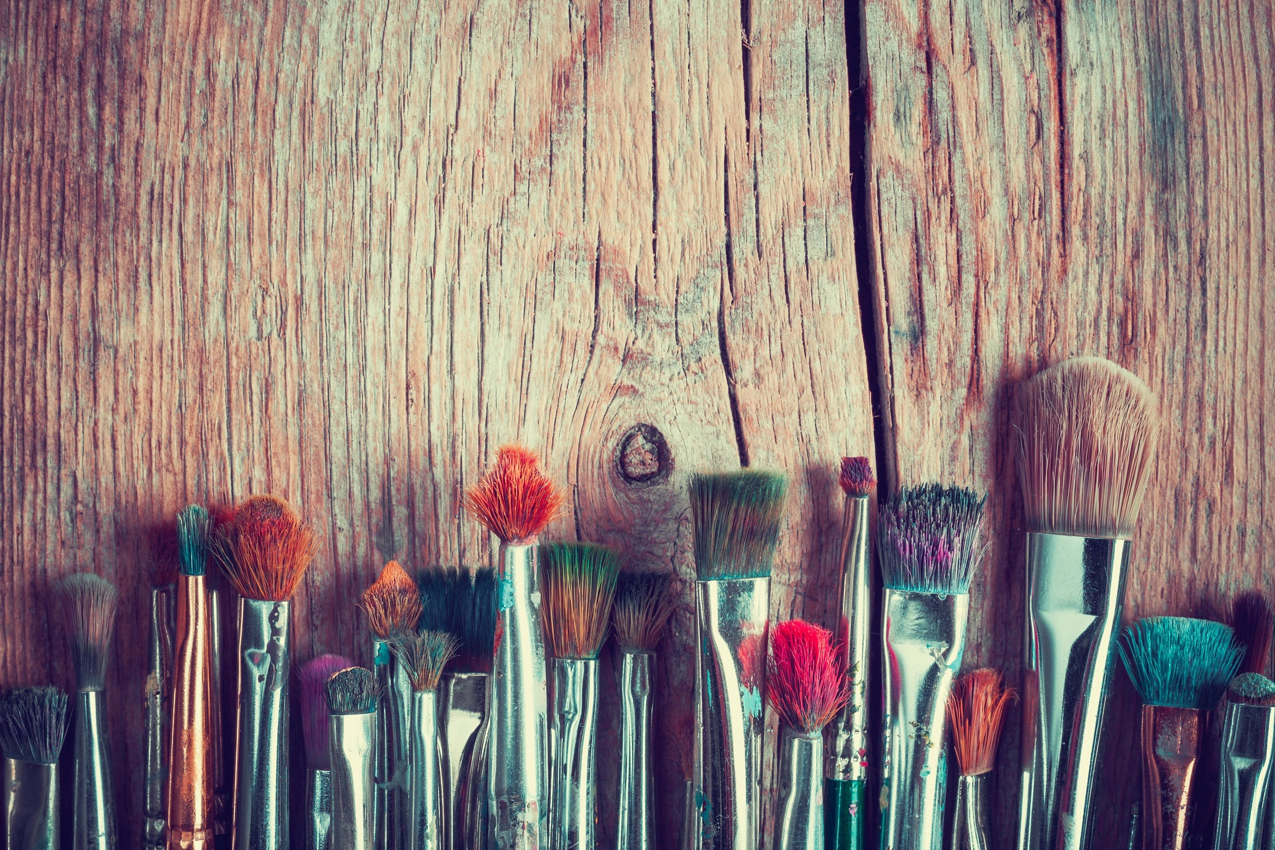 row of artist paintbrushes closeup on old wooden rustic table, retro stylized.