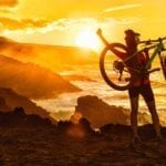 Success, achievement, accomplishment and winning concept with cyclist mountain biking. Happy MTB woman cycling raising arms lifting bike by sea during sunset cheering and celebrating at summit top.