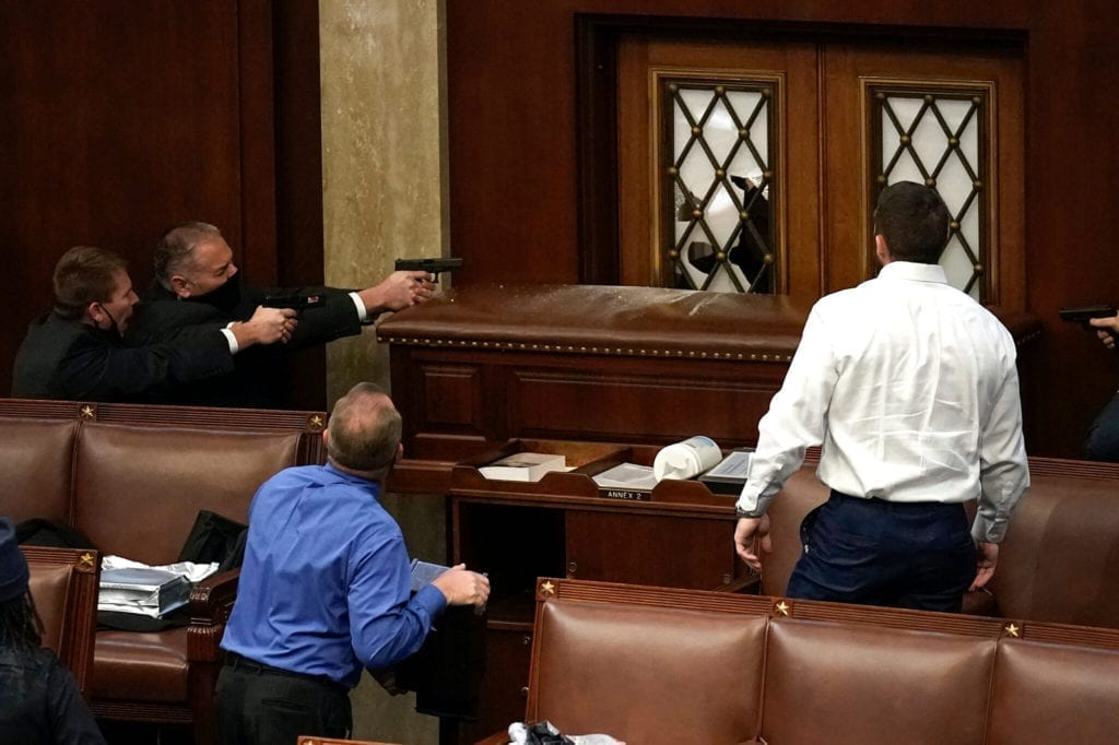 Police officers drew their guns inside the House chamber on Wednesday after pro-Trump protesters broke into the Capitol building and thousands swarmed the steps outside.