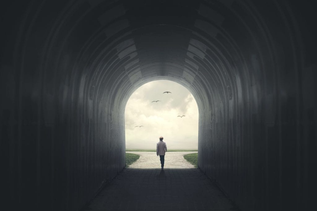 A man walking out of a tunnel coming onto a fork in the road.  Represents making decisions and possibility.