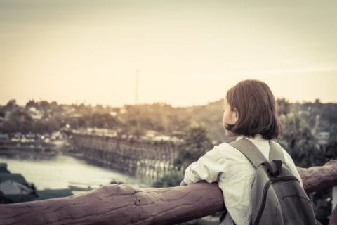 A girl looking out over a bridge.
