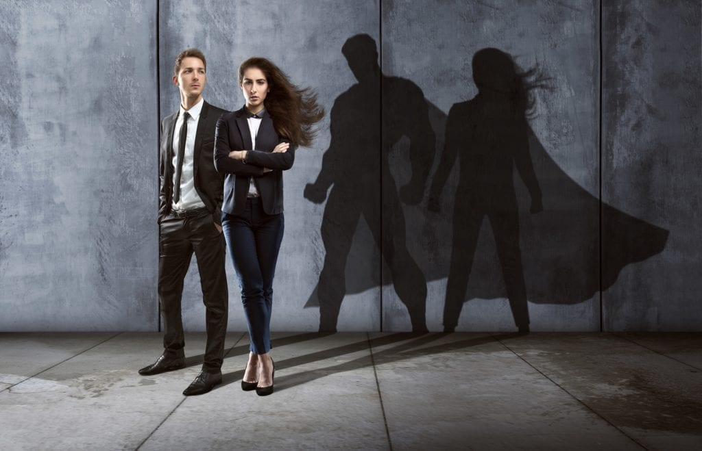 Two regular dressed people who are casting caped superhero shadows.  Meant to symbolize secret identity & superheroes.