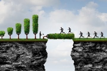 A picture of a person standing next to a cutdown tree with an axe & others crossing over that tree. Meant to symbolize a better type of profit that's more inclusive.