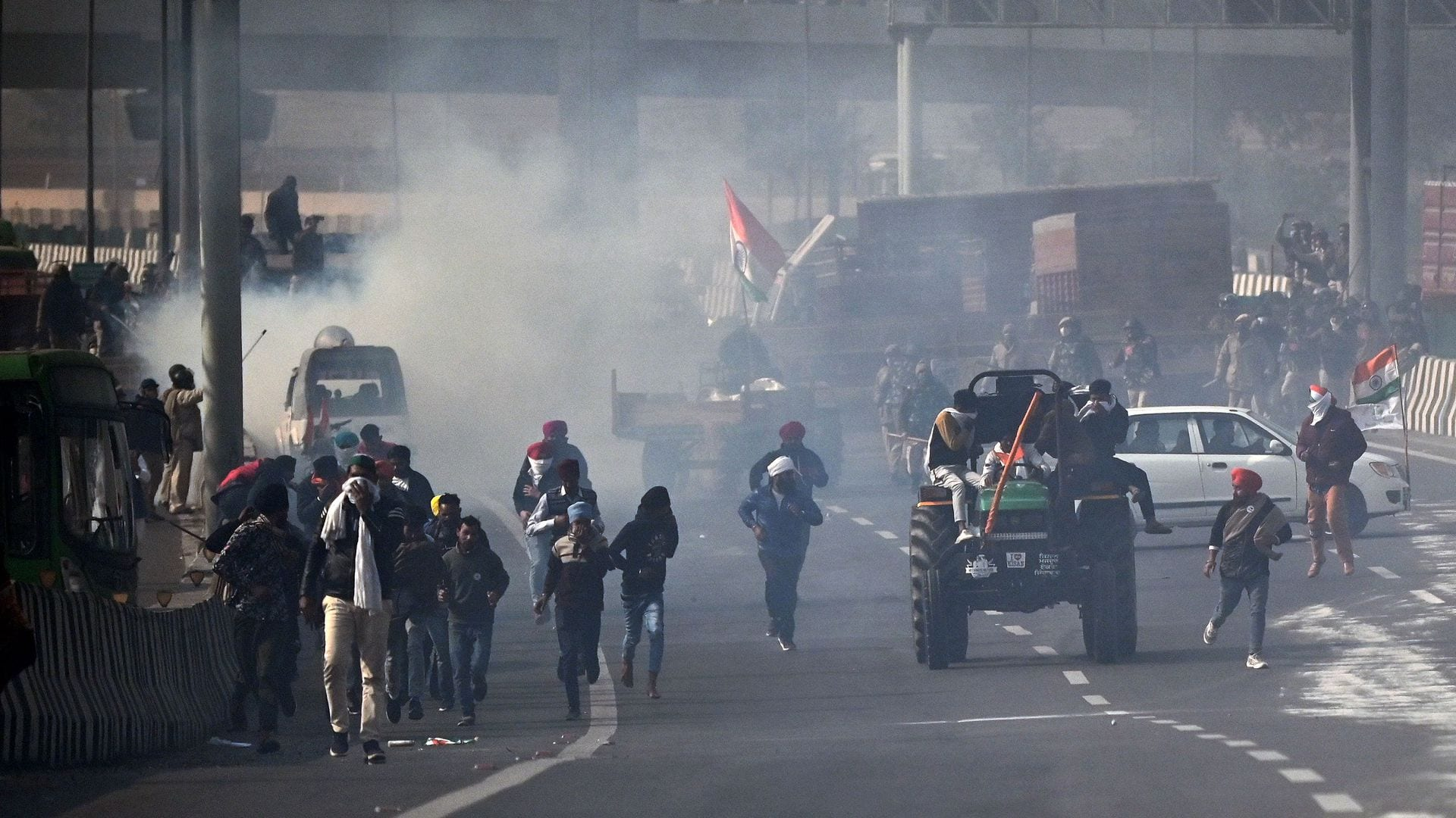 Farmers ride through the smoke of tear gas fired by the police as they protest the Indian central government's recent agricultural reforms in the capital New Delhi on Tuesday.