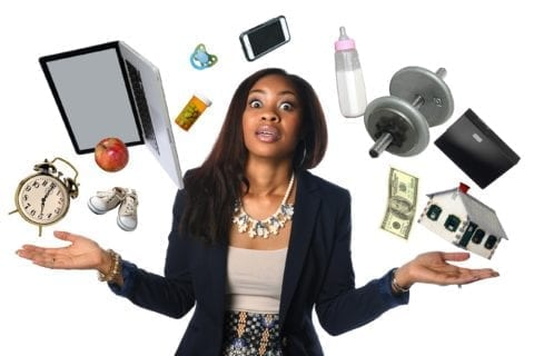 African American businesswoman juggling many objects and feeling overwhelmed.