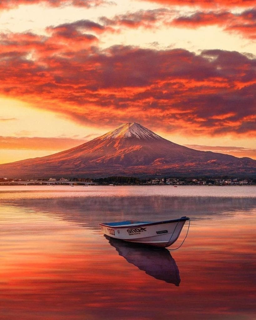 A Picture of Mount Fuji with a boat in front of it on a body of water.