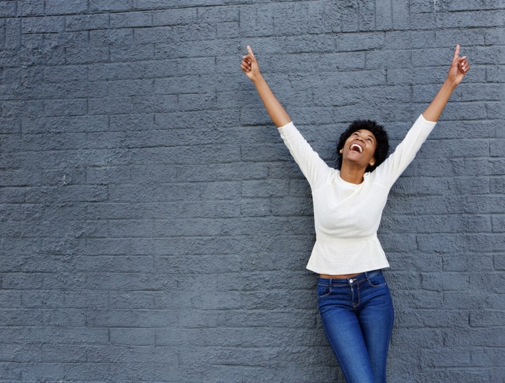 Portrait of a cheerful Black woman with hands raised pointing up.