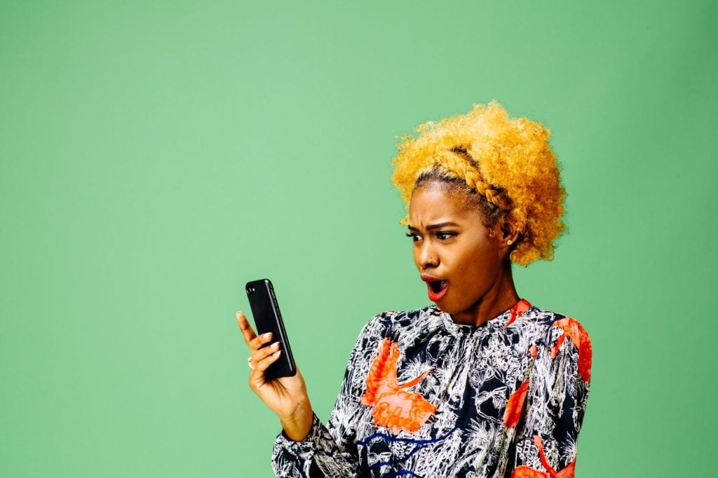 Black Woman looking at her phone with mouth wide open, isolated on green studio background.