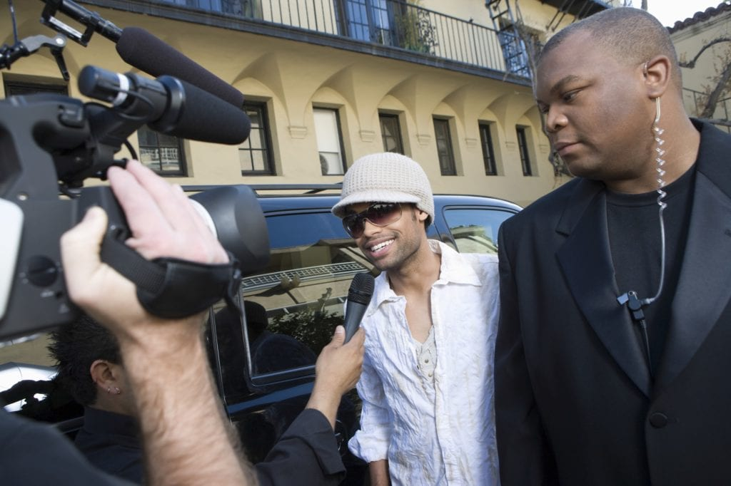 A fictional Black male celebrity with bodyguard being interviewed by paparazzi.