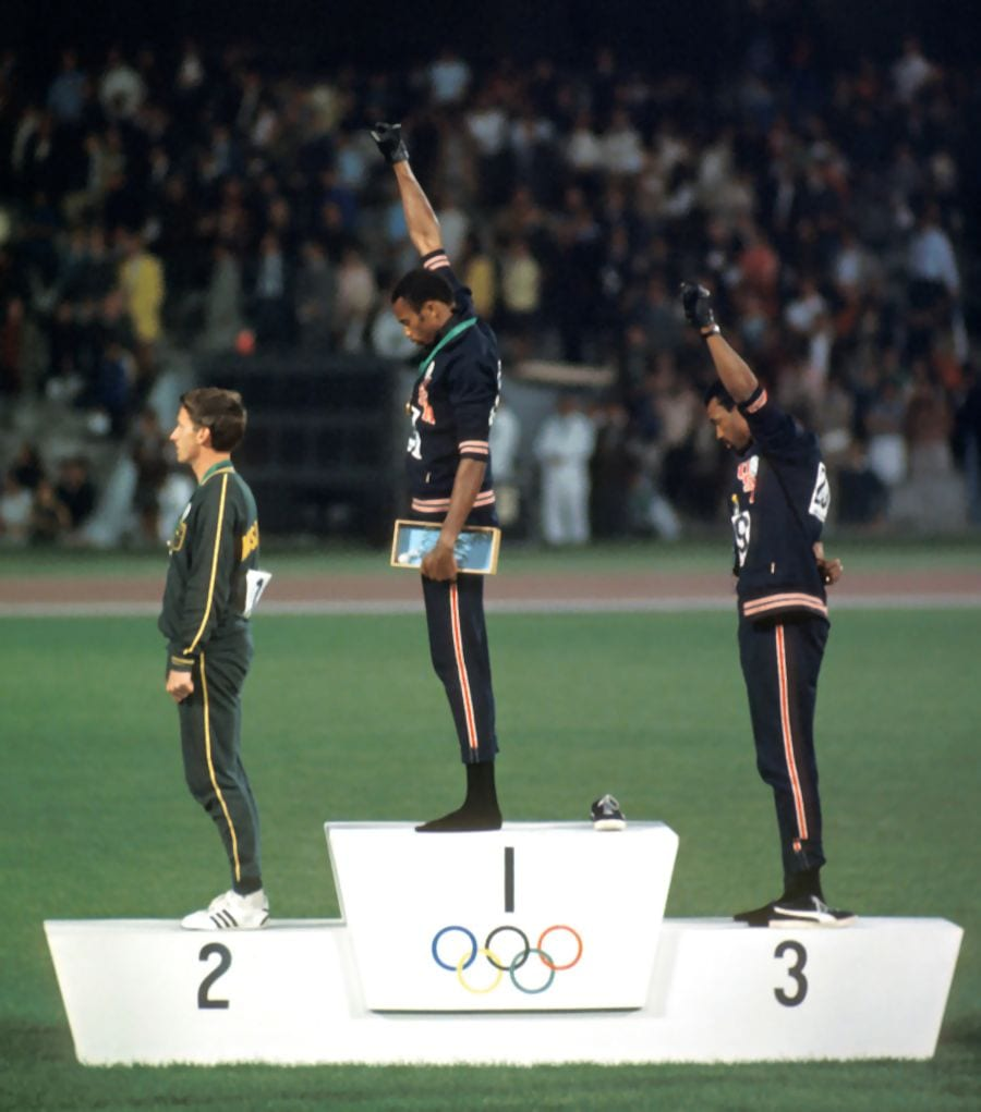 Black athletes Tommie Smith and John Carlos raise gloved fists at a medal ceremony during the 1968 Summer Olympics.