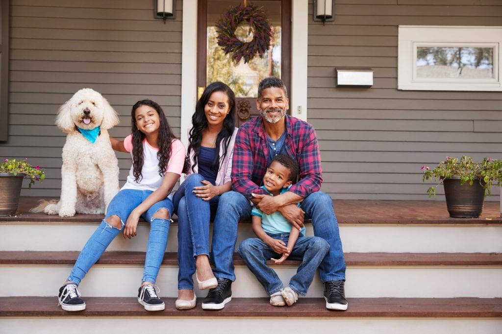 Black Family With Children And Pet Dog Sit On Steps Of Home.