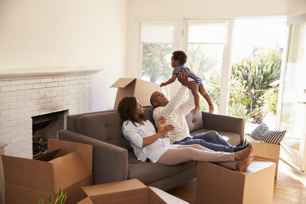 Black Parents Take A Break On Sofa With Son On Moving Day.