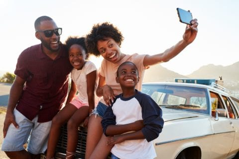 Black Family Posing For Selfie Next To Car Packed For Road Trip.