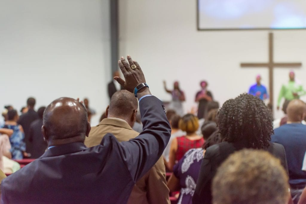 Black/African American Man at Church with His Hand Raised.