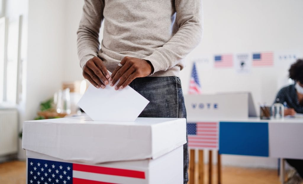 A Black man (unseen) casting a vote, and a Black woman is behind him in the background out of focus.