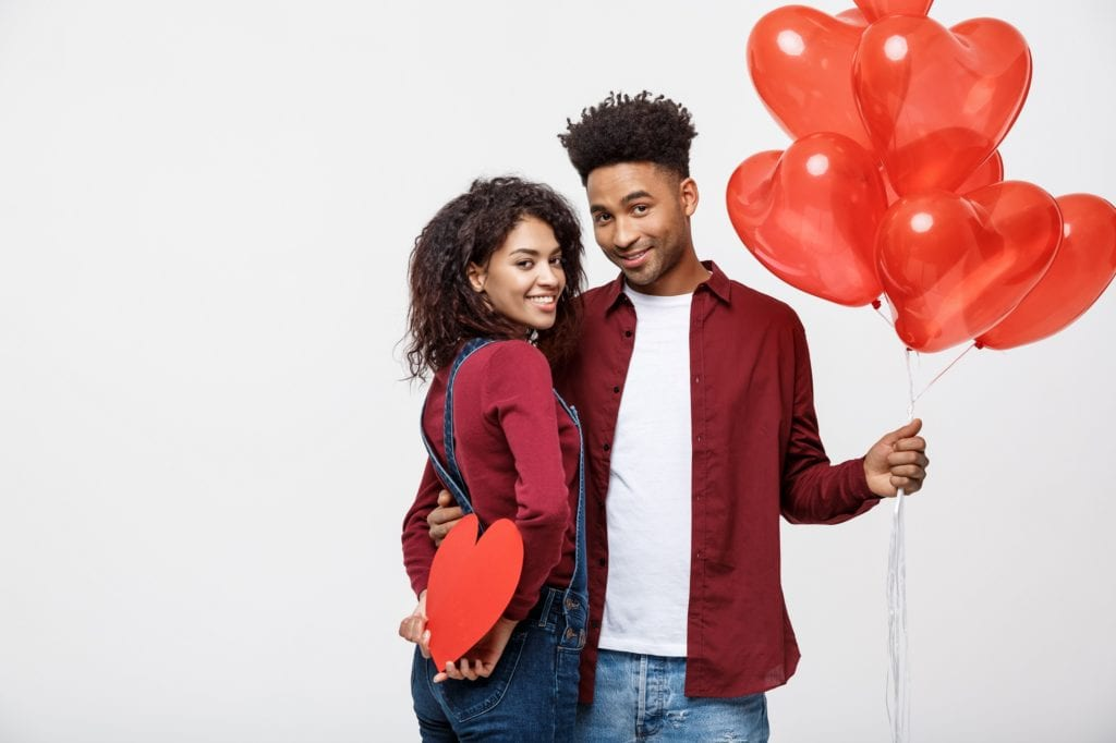 Young attractive Black couple holding heart balloon and paper staring at the viewer..