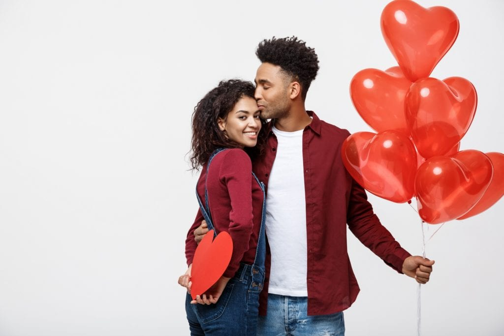 Young attractive Black couple holding heart balloon and paper sharing a sweet embrace.