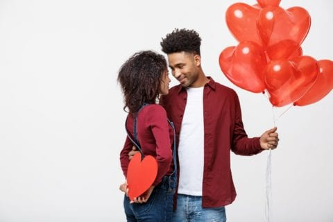 Young attractive Black couple holding heart balloon and paper staring lovingly at each other while embracing.