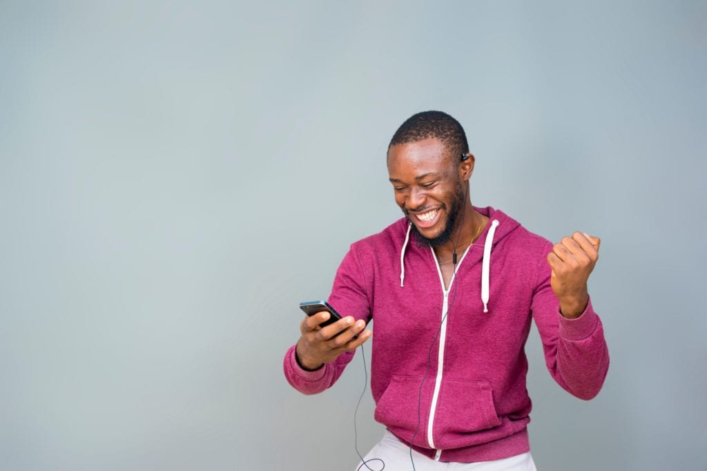 Young Black man happy and excited and celebrating while looking at his mobile phone.