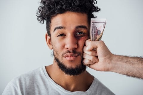Black man with bruised eye looking at camera near male hand holding cash isolated on grey.
