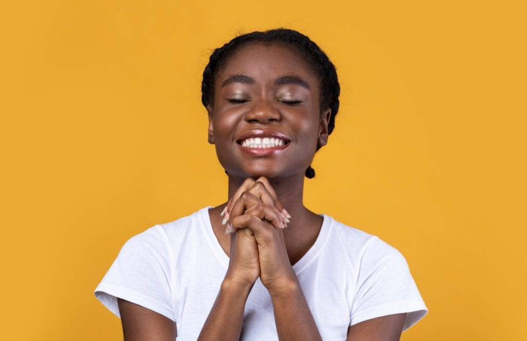 Hope Concept. Black Young Woman Praying God Holding Hands In Prayer Gesture Smiling With Eyes Closed Over Yellow Background.