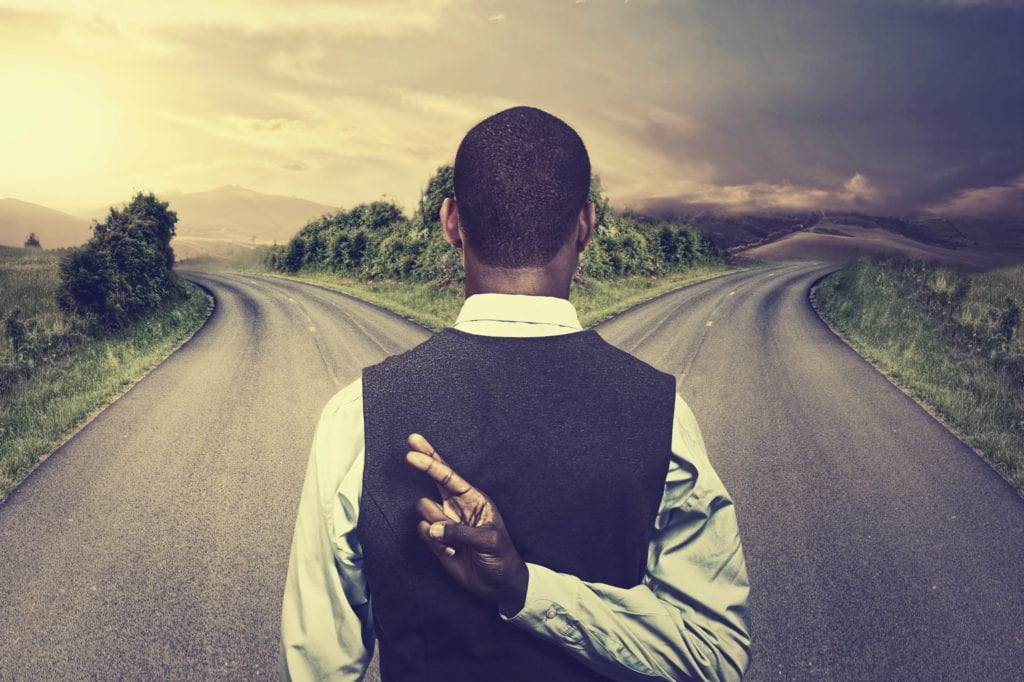 businessman in front of two roads crossing fingers hoping for best taking chance.
