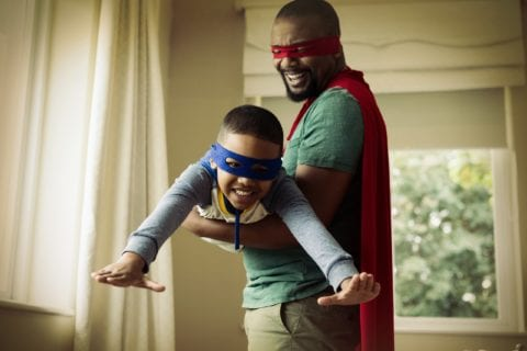 Smiling son and father pretending to be a superhero at home.