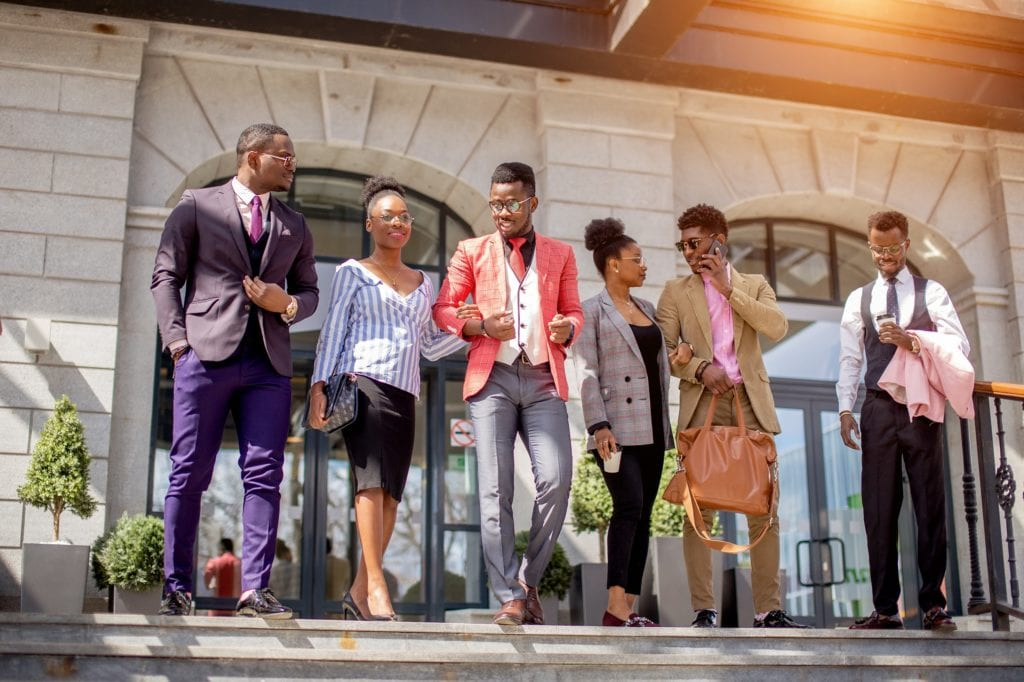 A group of well-dressed young Black professional going down stairs together.