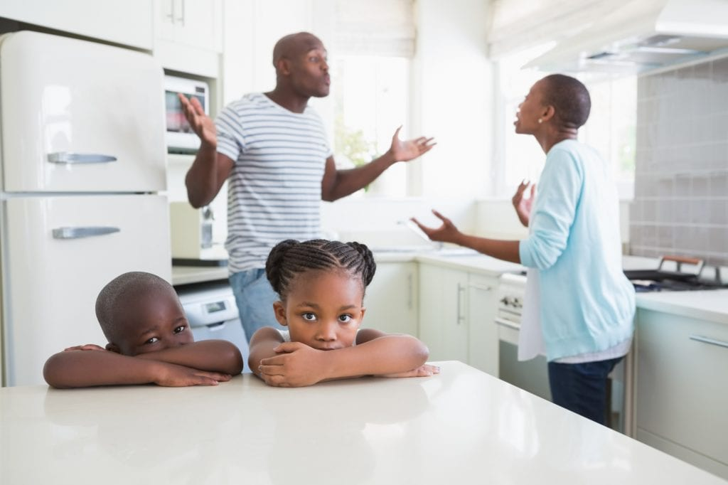 Couple having an argument in the kitchen in front of their kids (who look disappointed and hurt).