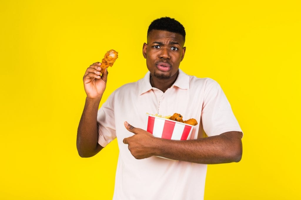 African American young guy eats fast food, chicken leg and a whole bucket in his hands. Emotions of condemnation and constraint. Yellow background.