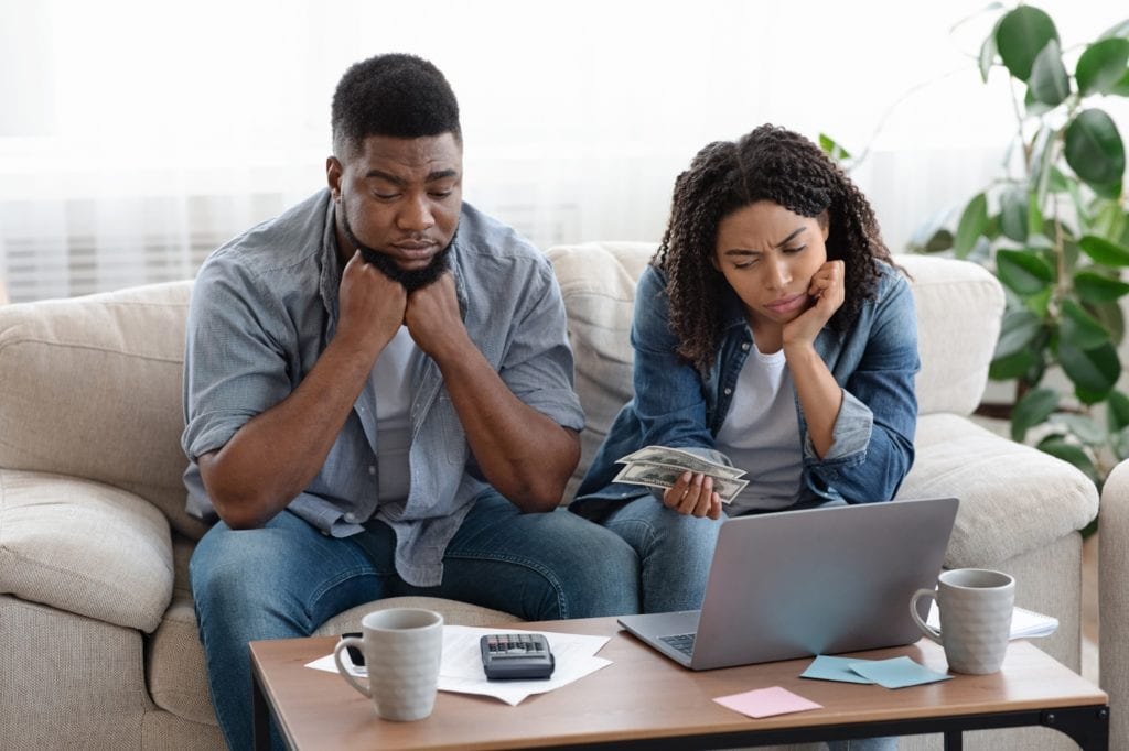 Financial Problems. Upset Black Couple Managing Family Budget Together At Home, Counting Remaining Money, Suffering From Crisis.