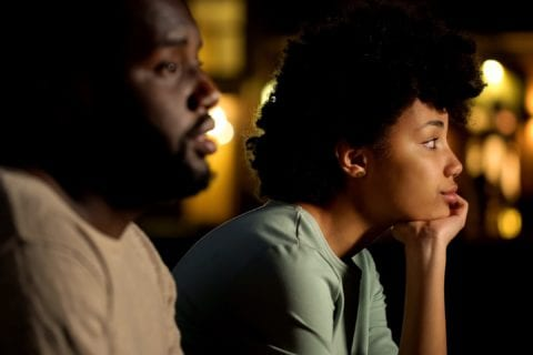 Disappointed looking Black couple sitting down together looking off into the distance.