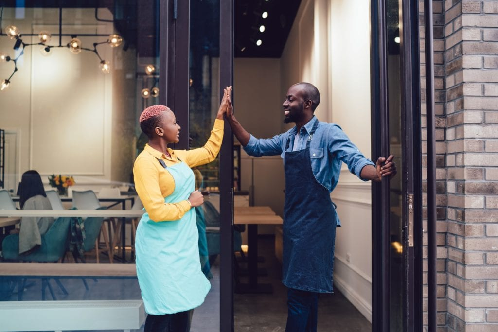 Joyful Black business partners in uniform looking at each other and giving high five while standing on entrance of own cafe and celebrating successful start.