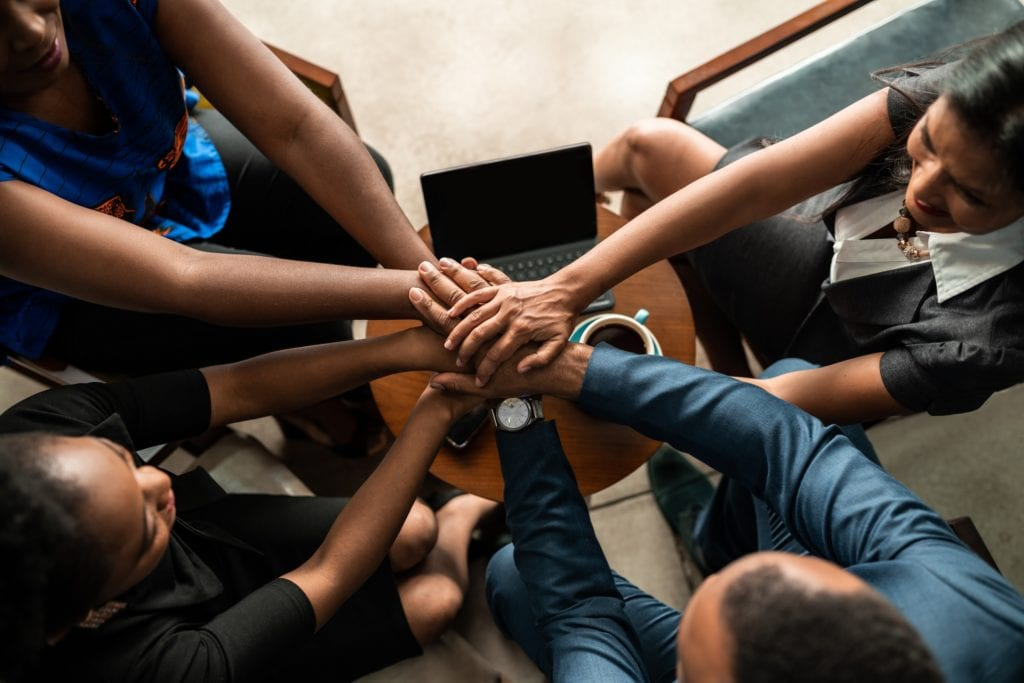 Top view of business team with hands stacked together in unity and trust.
