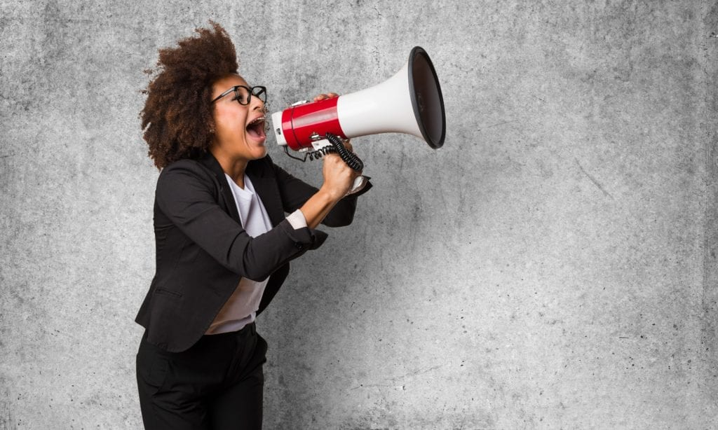 Black business woman shouting on the megaphone.