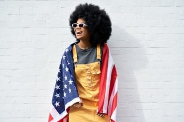 Black woman with an afro wearing yellow overalls while draped in an American flag leaning against a white wall.
