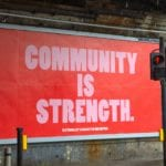 A street sign advertisement that reads Community is strength.