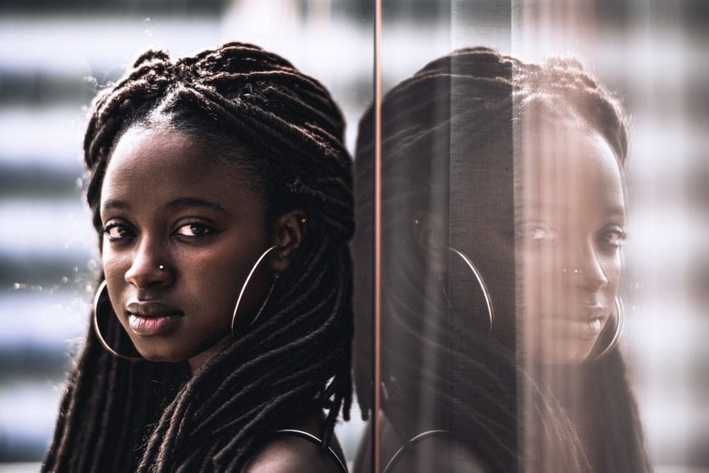 A portrait of a young dazzling Black woman with big earrings, nose piercing, and beautiful dreadlocks, she is looking at the camera while leaning against a glass wall which fully reflects her.
