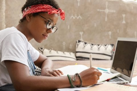 Black Woman with piercings and short hair writing with pen and paper in front of a laptop at a desk while wearing a bandana tied around her forehead.