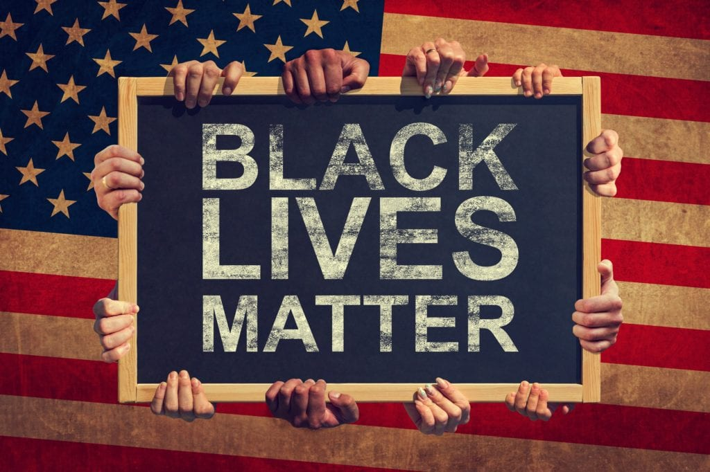 A lot of hand are holding a banner with text BLACK LIVES MATTER on background of American flag.