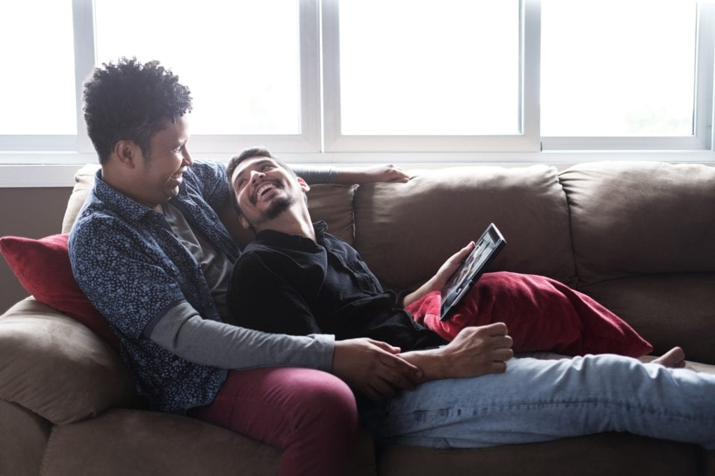 Male partners and friends looking at pictures on tablet at home - happily not settling.