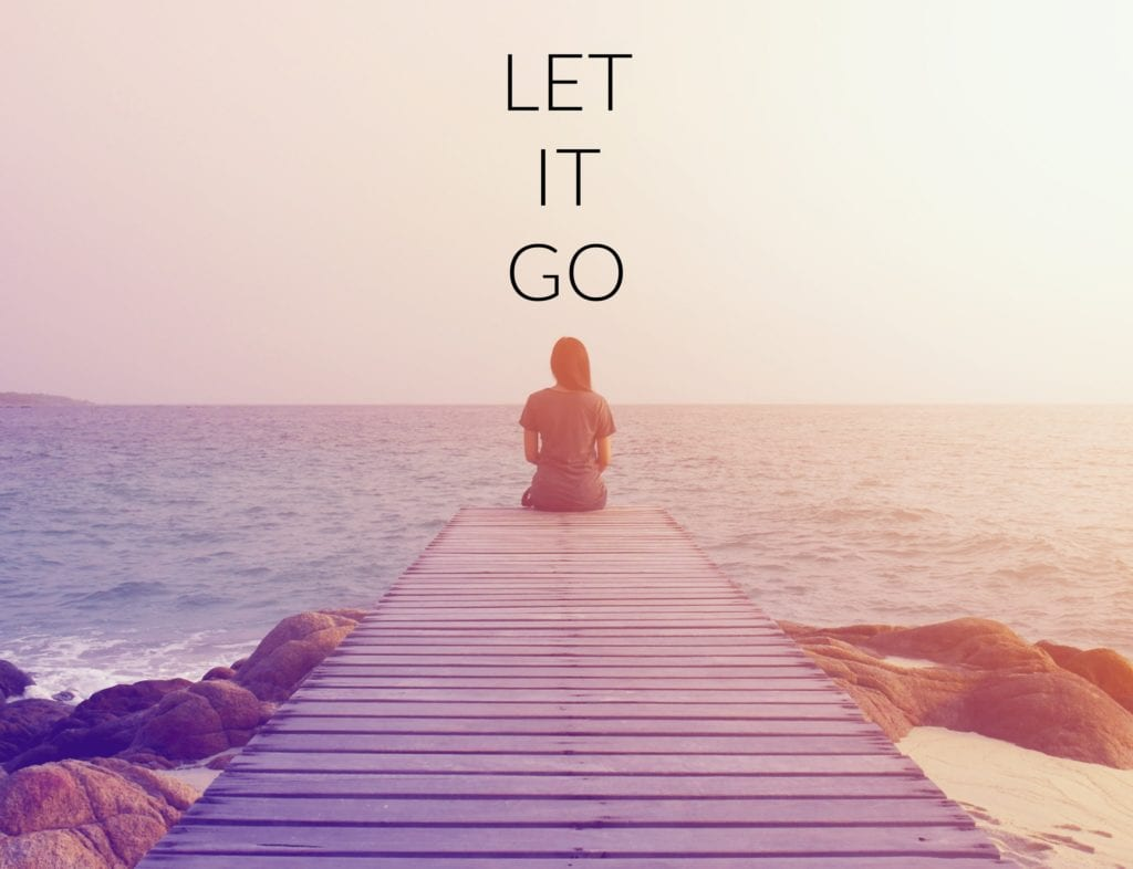 Get Up Concept - Inspirational quote on blurred background with vintage filter - woman sitting on a dock with the words Let It Go written above her head.