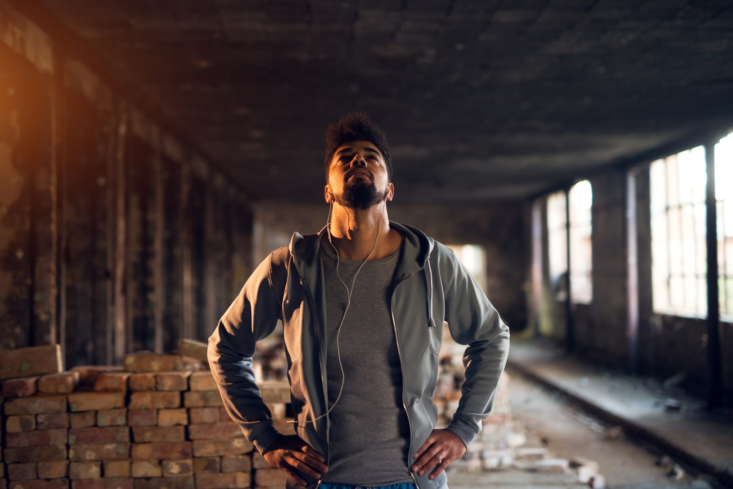 Bearded man in sportswear standing in abandon place with earphones and looking up.