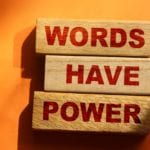 The phrase Words Have Power on wooden blocks laying on orange background.