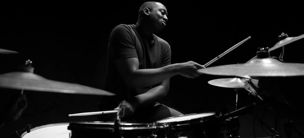 A black and white photo of drummer Larnell Lewis playing the drums.
