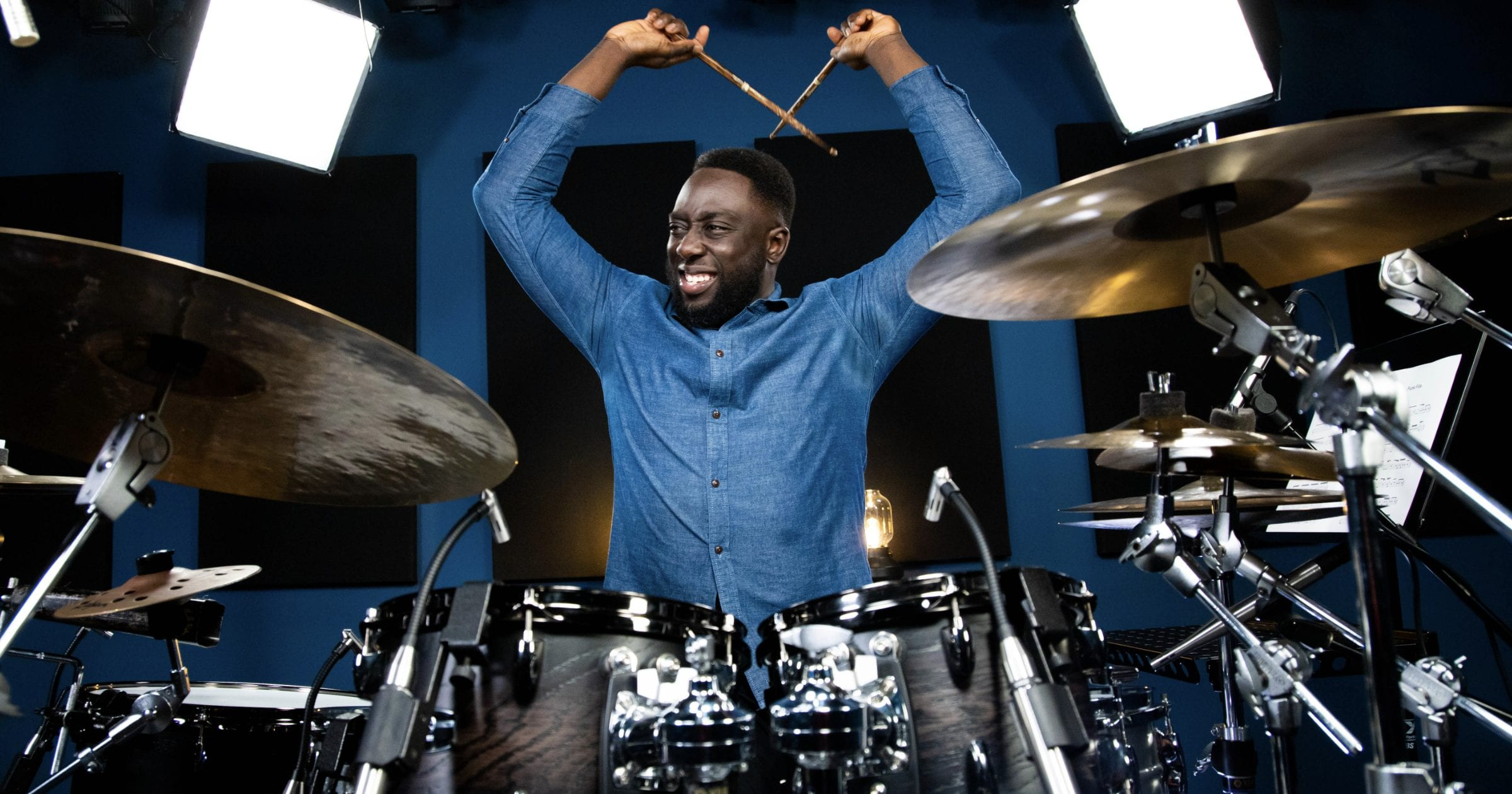 A picture of drummer Larnell Lewis going hard on the drums. Looks like a final crash on the cymbals is taking place.